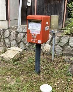 空き地にポツンとある郵便ポスト