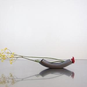 弓形の花器に曲線の茎をみせる―1/光峰窯