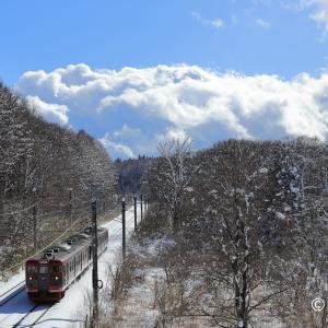 流れる雪雲と115系