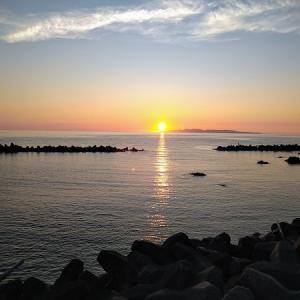 水平線に沈む夕日と岩牡蠣の燻製を満喫