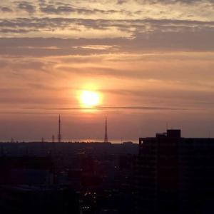 二本のアンテナの間へ沈んでいく太陽。