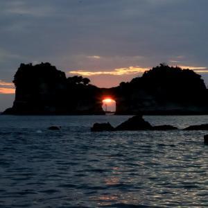 円月島の海蝕洞に沈む夕日と四双島 ( しそじま )灯台