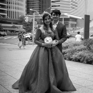 摩天楼街で記念撮影をする新婚カップル