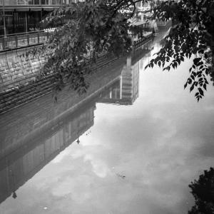 梅雨明け間近な夏空を映す川