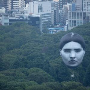 実在人物の巨大な顔、東京の空に浮遊