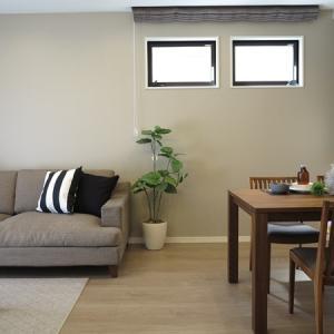グレージュ色のフローリングにウォールナット無垢材の家具を合わせたコーディネート