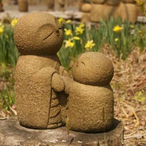 「心は濃厚接触で」。石んこ地蔵の背中に文字彫り。どんぐりの芽が出てます。