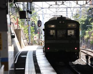 駅を発車して行くJR103系 NS407編成