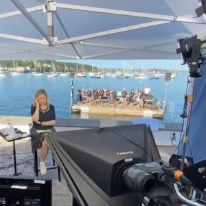 ニュースの生放送で、背景に予期せぬ合唱隊が!見事なアカペラにレポータ困惑