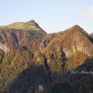 秋色に染まる山々の先に