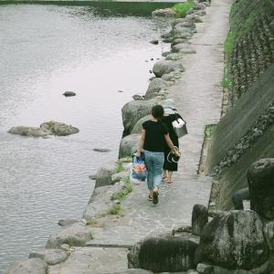 GA645Ziと川沿いを歩く人達