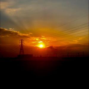雲間から飛び出した朝日と鉄塔