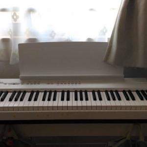 窓際に白い電子ピアノがある小さなダイニング